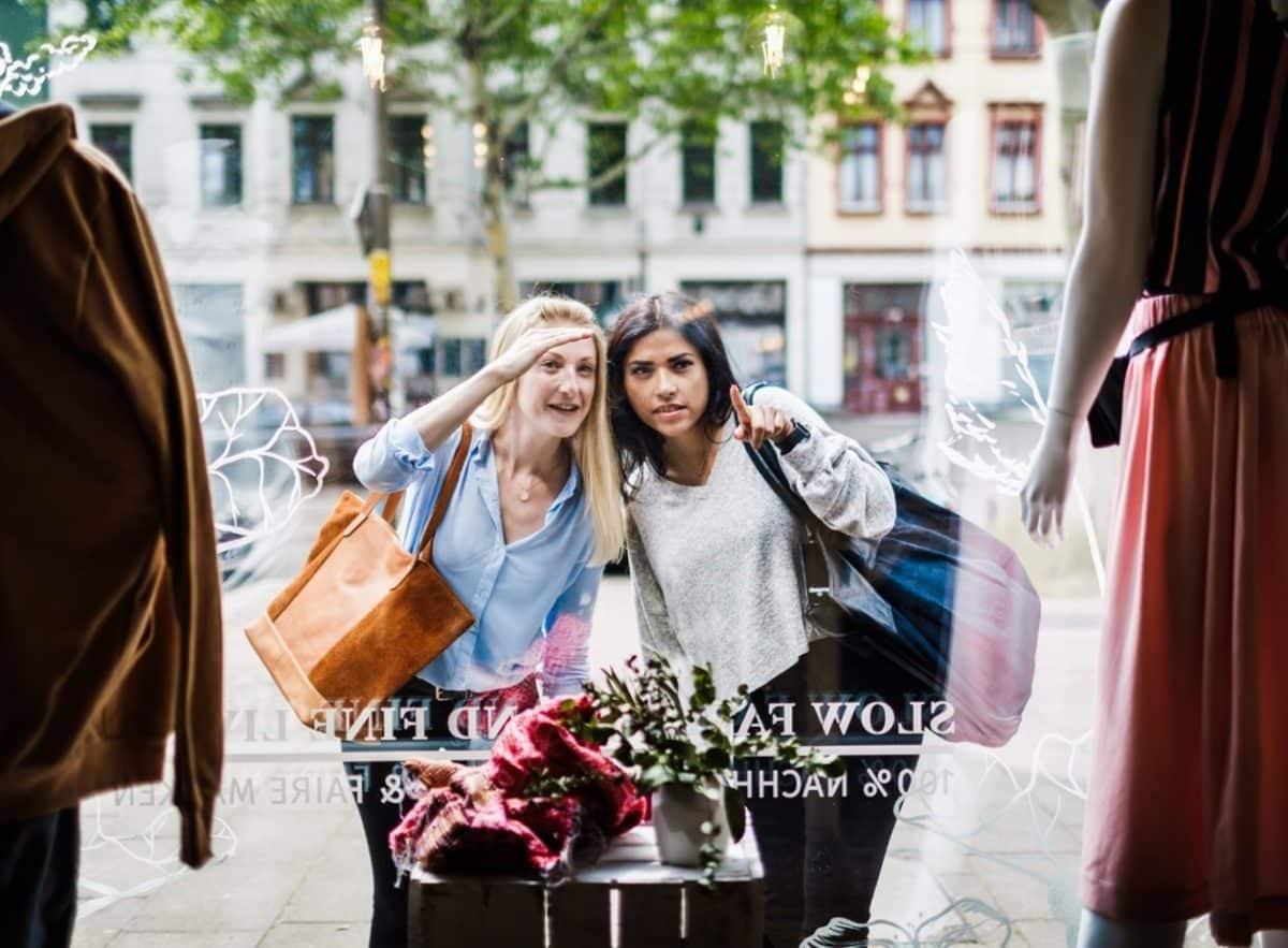 Zwei Frauen bewundern Schaufenstergestaltung eines Modegeschäfts