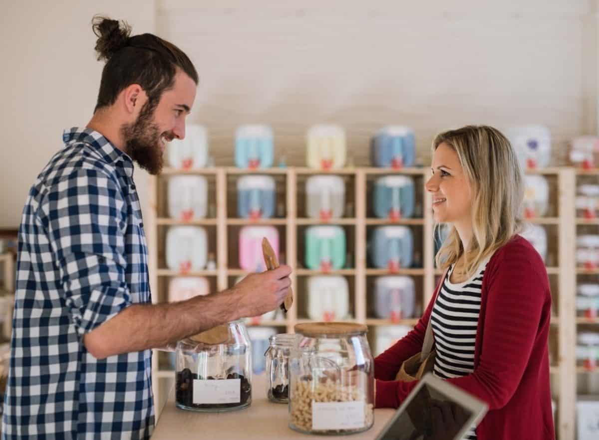 Verkäufer wendet Verkaufsstrategie für den Einzelhandel an, um Kundin zu überzeugen.