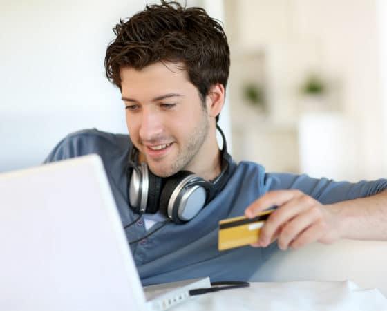 man heeft creditcard vast terwijl hij laptop gebruikt