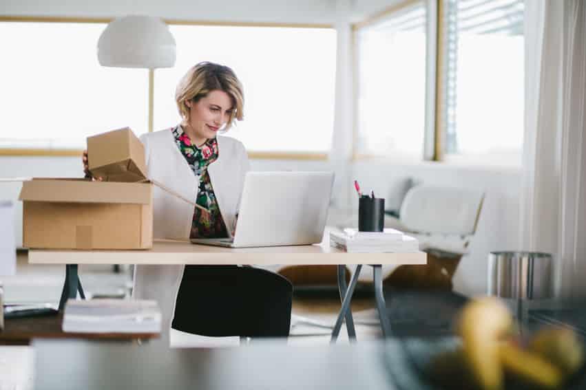 vrouw pakt pakket in thuis webshop