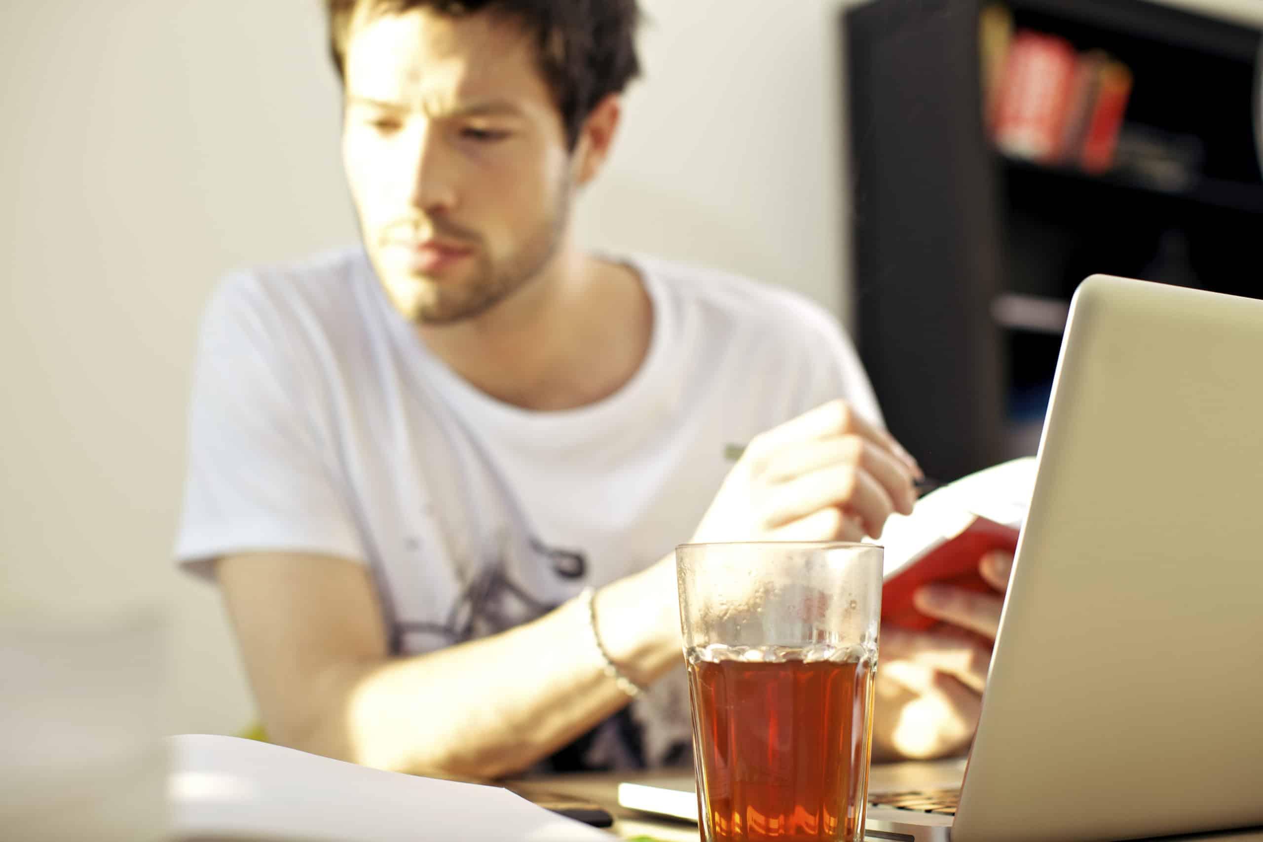jonge man aan het werk met glas drinken