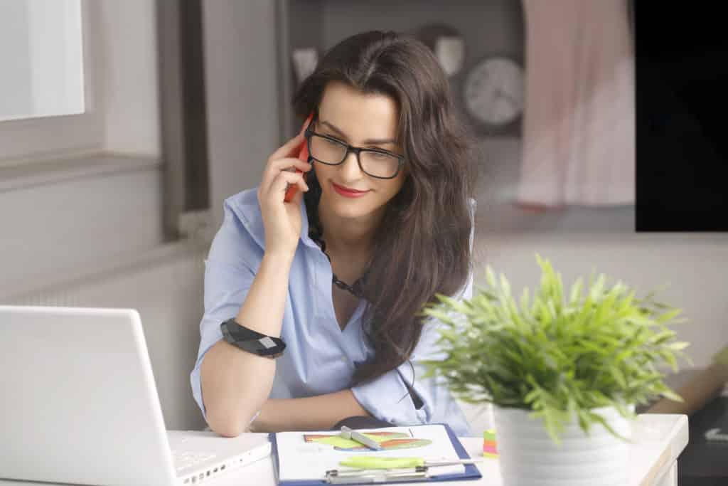 jonge zakenvrouw met laptop en charts belt